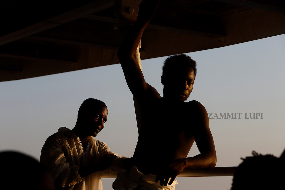 Rescued migrants stand on the deck of the Migrant Offshore Aid Station (MOAS) ship MV Phoenix between Libya and the Italian island of Lampedusa, August 3, 2015.  118 migrants were rescued by the Phoenix from a rubber dinghy some 20 miles (32 kilometres) off the coast of Libya on Monday morning. The Phoenix, manned by personnel from international non-governmental organisations Medecins san Frontiere (MSF) and MOAS, is the first privately funded vessel to operate in the Mediterranean.<br /> REUTERS/Darrin Zammit Lupi <br /> MALTA OUT. NO COMMERCIAL OR EDITORIAL SALES IN MALTA