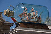 Looking upwards from below, we see above us artist Yinka Shonibare's artwork called Nelson's Ship in a Bottle on the Fourth Plinth in London's in Trafalgar Square. The artwork features a 1:29 scale replica of Lord Nelson's original HMS Victory commemorating the Battle of Trafalgar in 1805, Shonibare said his version with its textile sails with African and batik prints reflects the multicultural and diverse capital. The 2.35m high ship inside a specially-made glass bottle, will be in place for 18 months. 37 large sails are made of patterns which are commonly associated with African dress and culture. The patterns also look back at the path of colonialism as the patterns were inspired by Indonesian batik design, which were mass produced by the Dutch and sold to the colonies in West Africa. The Fourth Plinth is in the north-west of Trafalgar Square