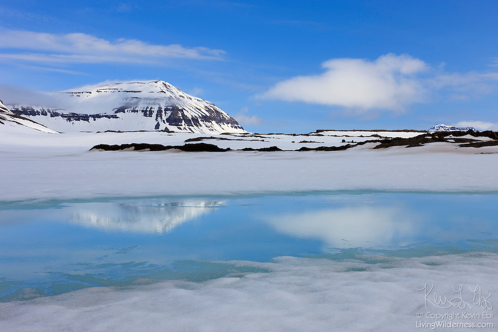 Vestdalsheiði, a mountain in eastern Iceland, is reflected in a narrow stretch of a lake that has recently thawed.