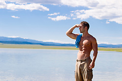 good looking man looking off in the distance by a lake in New Mexico