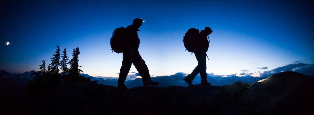 Ian Derrington (shown twice) hikes Salvation Peak by headlamp in North Cascades National Park, Washington.