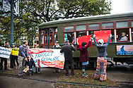 A streetcar passes the New Orleans Friday highschool climate strike on St. Charles Avenue.