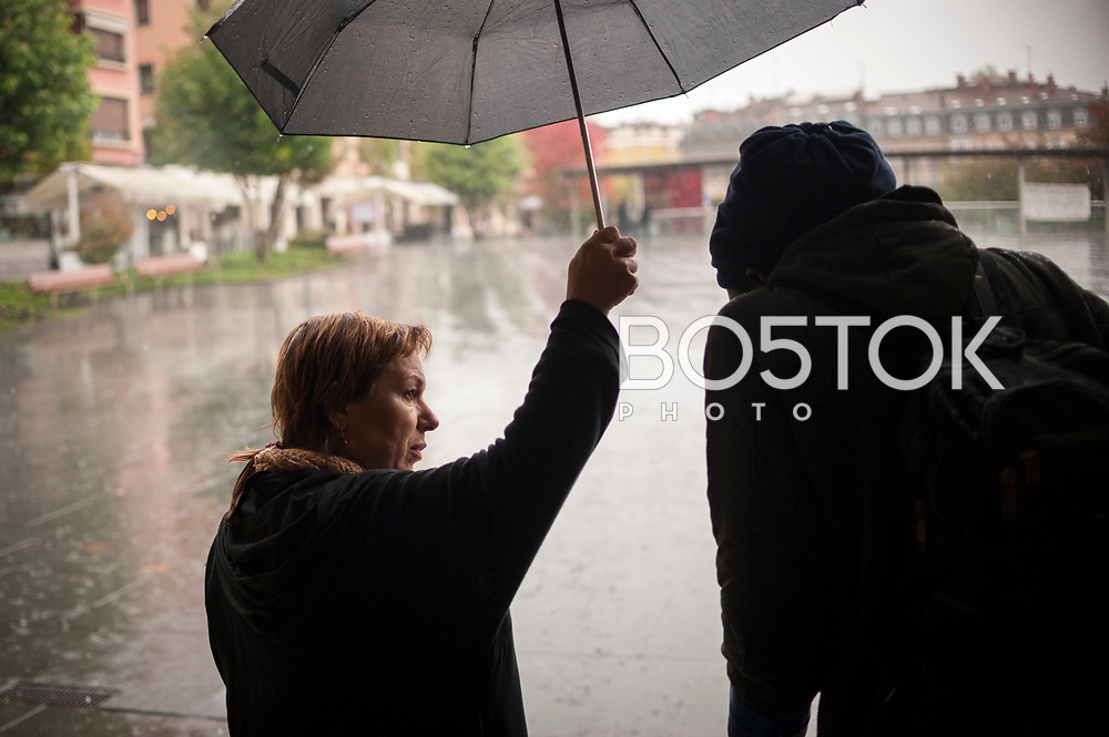 A volunteer with an umbrella covers an African migrant walking with crutches. Irun (Basque Country). November 1, 2018. A group of volunteers has created a host network to serve migrants and inform about the public services they are entitled to and the ways to cross the border. This group of volunteers is avoiding a serious humanitarian problem Irun, the Basque municipality on the border with Hendaye. As the number of migrants arriving on the coasts of southern Spain incresead, more and more migrants are heading north to the border city of Irun. French authorities have reacted by conducting random checks as far as the city of Bordeaux, more than 200 kilometers north of the border. Migrants who are caught are then deported back to Irun. (Gari Garaialde / Bostok Photo).