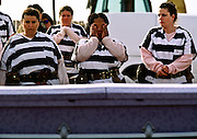 """01 NOVEMBER 1999  - PHOENIX, ARIZONA, USA: Members of the women chain gang in Maricopa County, Phoenix, AZ, weep  while they bury a homeless person in the county's """"Potter's Field"""" or cemetery for the indigent. Maricopa county sheriff Joe Arpaio claims to have the only women's chain gang in the United States. He has been criticized for the chain gang but claims to be an """"equal opportunity incarcerator."""" He has said that if puts men on a chain gang he will also put women on a chain gang. The women are prisoners in the county jail and volunteer for duty on the chain gang because it gets them out of the jail for six hours a day. The chain gang also buries the county's homeless and indigents.   © Jack Kurtz  WOMEN   PRISON   CIVIL RIGHTS  SOCIAL ISSUES    POVERTY"""