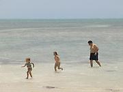 Father with his daughters playing on the beach Florida Keys