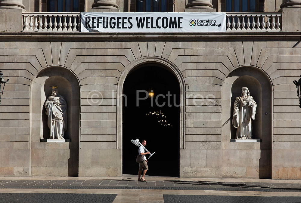 Refugees Welcome sign in front of Barcelonas City Hall, also known as the Casa de la Ciutat, stands on one side of the Plaça Sant Jaume, right in the middle of Barcelonas Gothic Quarter, Barcelona, Spain. Barcelona launched a municipal plan to welcome refugees fleeing wars from places like Syria and Iraq.