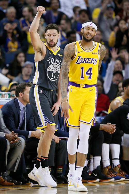 Golden State Warriors guard Klay Thompson (11) makes a three point basket against Los Angeles Lakers forward Brandon Ingram (14) in the second half of an NBA game at Oracle Arena on Saturday, Feb. 2, 2019, in Oakland, Calif. The Warriors won 115-101.