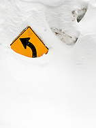 Curve ahead highway warning sign sticking out of deep snow, along the road to Paradise, Mount Rainier National Park, Washington, USA