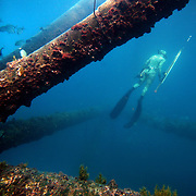 Kelsey Albert scans the waters for fish below a tower while Freediving and spearfishing off the coast of North Carolina