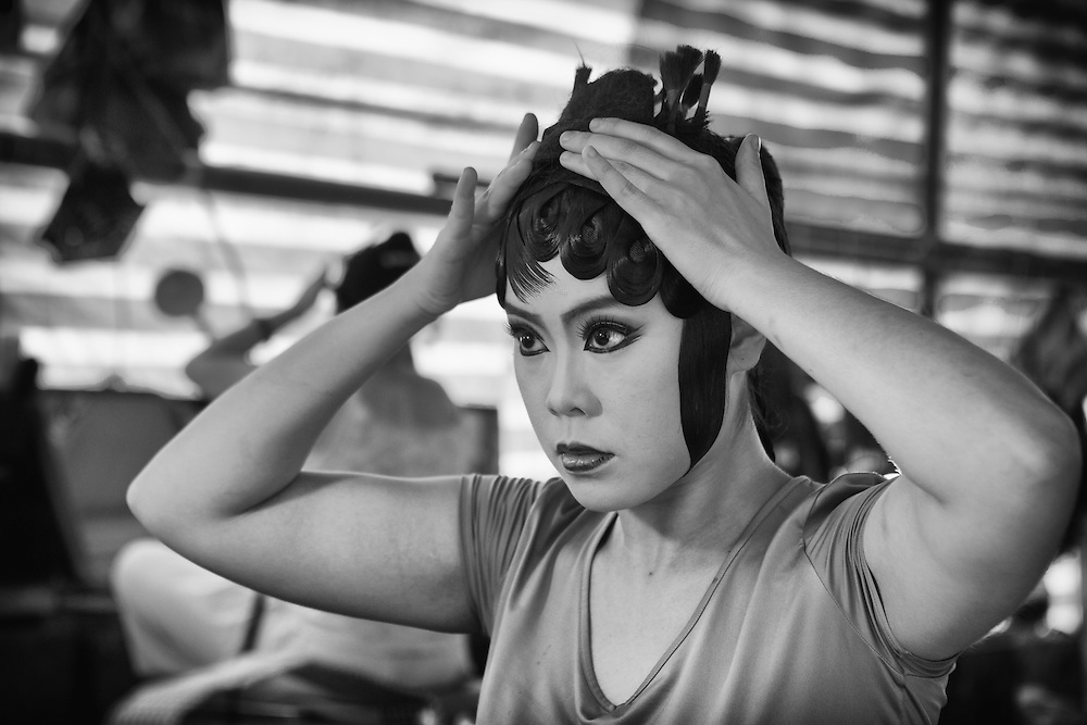 A Chinese opera performer from the I-Hsin opera troupe adjusts her hair in preparation for a performance