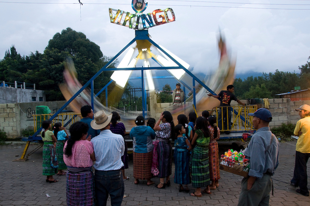 """Girls wait anxiously in line for a turn on the """"Vikingo"""" ride during a celebration in San Pedro la Laguna.  People from all other cities surrounding Lago de Atitlan gather for celebrations, each group wearing unique clothing designs and styles to identify their culture.  San Pedro la Laguna, Lago de Atitlan, Guatemala, June 2009.  (Photo/William Byrne Drumm)"""