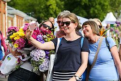 © Licensed to London News Pictures. 25/05/2019. London, UK. Women take a selfie at the RHS Chelsea Flower Show after purchasing flowers sold off cheap by the exhibitors on the final day of the show. The Royal Horticultural Society Chelsea Flower Show is an annual garden show held in the grounds of the Royal Hospital Chelsea in West London since 1913. Photo credit: Dinendra Haria/LNP