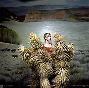 20 something female standing behind dramatic yucca plant in front of painted plains backdrop