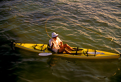 Stock photo of an aerial view of a man fly fishing from his yellow kayak