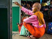 26 OCTOBER 2015 - YANGON, MYANMAR:  A Burmese nun sits in the doorway of the Yangon Circular Train. The Yangon Circular Railway is the local commuter rail network that serves the Yangon metropolitan area. Operated by Myanmar Railways, the 45.9-kilometre (28.5mi) 39-station loop system connects satellite towns and suburban areas to the city. The railway has about 200 coaches, runs 20 times daily and sells 100,000 to 150,000 tickets daily. The loop, which takes about three hours to complete, is a popular for tourists to see a cross section of life in Yangon. The trains run from 3:45 am to 10:15 pm daily. The cost of a ticket for a distance of 15 miles is ten kyats (~nine US cents), and for over 15 miles is twenty kyats (~18 US cents).     PHOTO BY JACK KURTZ