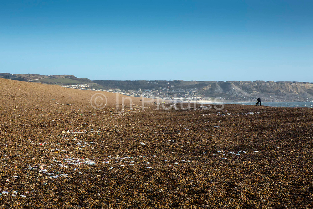 Landscape view of cigarette packets which have been washed up on Chesil Beach from a cargo container ship accident on Jurassic Coast of Dorset, UK.