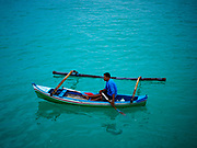 03 AUGUST 2017 - KUTA, BALI, INDONESIA: A man paddles his outrigger canoes towards the Indian Ocean from Jimbrana Beach in Kuta. The beach is close to the airport and a short drive from other beaches in southeast Bali. Jimbrana was originally a fishing village with a busy local market. About 25 years ago, developers started building restaurants and hotels along the beach and land prices are rising. The new emphasis on tourism is changing the nature of the area but the fishermen are still busy very early in the morning.    PHOTO BY JACK KURTZ