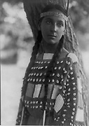 Young Native American woman, half-length, portrait, standing, facing front, 1907.