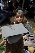 A young woman graduand wearing a rented gown and mortarboard at a private drinks party before their university graduation ceremony, on 13th July 2017, at the University of York, England.