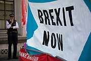 Brexit Now banner and a senior policeman outside The Supreme Court as the second day of the hearing to rule on the legality of suspending or proroguing Parliament begins on September 18th 2019 in London, United Kingdom. The ruling will be made by 11 judges in the coming days to determine if the action of Prime Minister Boris Johnson to suspend parliament and his advice to do so given to the Queen was unlawful.