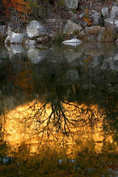 Stock photo of the reflection of boulders and trees in the river in the Texas Hill Country