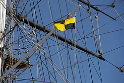 © Licensed to London News Pictures. 24/03/2020. London, UK. The Cutty Sark flies the Yellow jack or Lima flag . Historically this means that the ship is under quarantine in harbour because of disease on board. Last night the Government announced a lockdown to slow the spread of Coronavirus and reduce pressure on the NHS. Photo credit: George Cracknell Wright/LNP