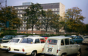Cars parked in car park by large modern office block, UK 1966 unknown location