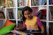 Giovana Lima do Rosa reading a book in the community library, Biblioteca Comunitaria do Arquipelago, Porte Alegre, Brazil. <br /> <br /> Cirandar is working in partnership with  C&A and C&A Instituto to implement a network of Community Libraries in eight communities of Porto Alegre.