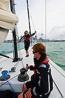 Sailing aboard a Sail NZ America's cup sailboat in Auckland Harbor (Waitemata Harbor), with the Auckland skyline behind,  Auckland, New Zealand