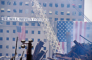 """22 SEPTEMBER 2011 - NEW YORK, NY: American flags and a banner hang from a building in the wreckage of the World Trade Center complex at """"Ground Zero"""" of the WTC terrorist attack, while recovery work continues Sept. 22, 2001.  More than 2,900 people were killed when terrorists crashed two airliners into the towers on Sept. 11, 2001.  PHOTO BY JACK KURTZ"""