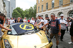 © Licensed to London News Pictures. 03/08/2019. London, UK. Supporters of Stephen Yaxley-Lennon, known as Tommy Robinson places a flag on a parked golden Lamborghini in central London. Last month Tommy Robinson was given a nine-month prison sentence at Old Bailey after he was found guilty of contempt of court. Photo credit: Dinendra Haria/LNP