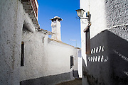 Narrow passage through the traditional whitewashed houses of Fondales, Las Alpujarras, Andalusia, Spain.