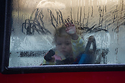 © London News Pictures. 25/04/2012. London, UK. A girl looking from the window of a red bus during heavy rain in central London on April 25, 2012. Photo credit : Ben Cawthra /LNP