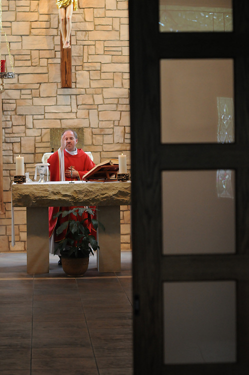 Father Pawel Bandurski of the Divine Mercy Polish Mission in Lombard leads a weekday mass for an attendance of two in a small chapel on campus.
