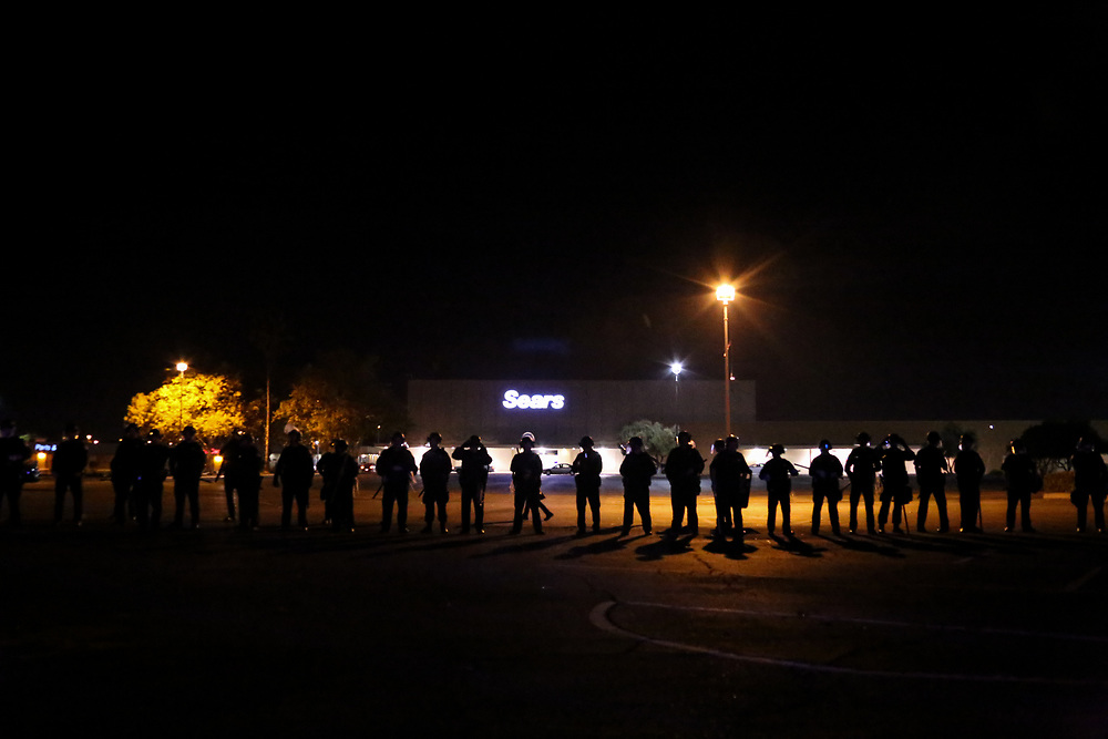 Police in riot gear line up in formation as crowds gather after a Ferguson grand jury's decision not to indict Ferguson, Missouri Police Officer Darren Wilson in the shooting death of Michael Brown, during a protest in Sacramento, Calif., Monday, November 24, 2014.