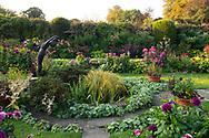 Borders of Dahlias around a pond and statue in the Sunken Garden at Chenies Manor Garden, Rickmansworth, Buckinghamshire, UK
