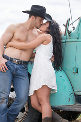 romantic cowboy and a girl together by a truck outdoors in a field