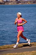 Adult woman age 26 jogging with tape around Lake Calhoun.  Minneapolis  Minnesota USA