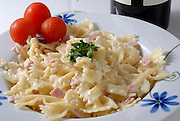 A plate of Bow tie farfalle Pasta in white sauce with red tomatoes ready to be served and eaten
