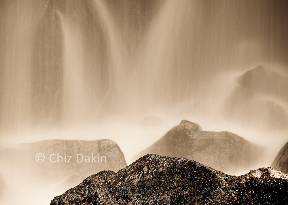 Sepia-toned abstract image of water flowing over rocks at the base of Lumsdale waterfall, Derbyshire