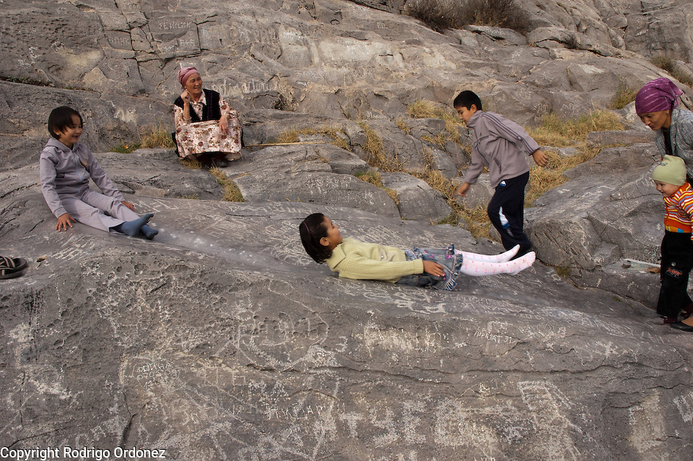 Children slide down Bel Orik (also known as Bel Tash), a smooth rock on the hillside of Sulaiman Too (Solomon's Mountain), in Osh (Kyrgyzstan). According to local beliefs, pilgrims sliding down the slope of this rock will find healing to their ailments, and women seeking to conceive will find fertility. Sulaiman Too is considered sacred and is included in UNESCO's Word Heritage List.