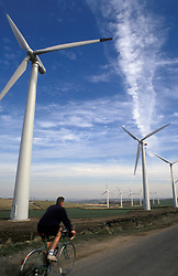 Cyclist passing wind turbines South Yorkshire UK