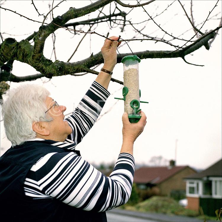 Freda Shaw hangs up a bird feeder in her garden in Ampleforth, North Yorkshire, UK