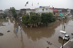July 3, 2018 - Lahore, Punjab, Pakistan - Pakistani Residents of China Scheme passing through flooded road after the intense monsoon rains in Lahore. The ongoing pre-monsoon rain spell has once again hit the city. At least six people were killed many injured in rain-related incidents. Mercilessly as 238mm rain continued three hours inundated most of the city areas resulting in worst traffic jams as well as serious inconvenience for the citizens. The Met Office has said that due to high pressure monsoon currents penetrating in the country, the Punjab capital, as well as other cities, will continue to receive downpour for the next two days. (Credit Image: © Rana Sajid Hussain/Pacific Press via ZUMA Wire)