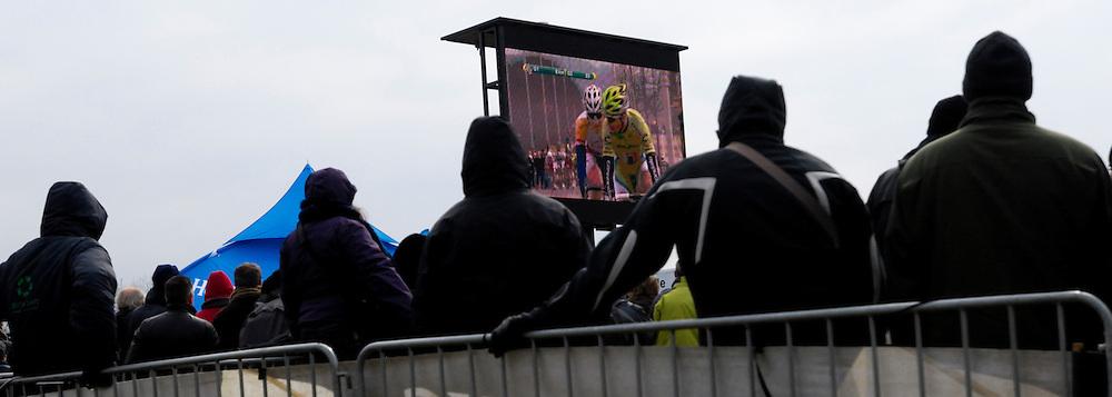 Belgium, March 31 2013: Spectators watch the final part of the Ronde van Vlaandaren 2013 cycle race on a big screen at the top of the Oude-Kwaremont. Copyright 2013 Peter Horrell.