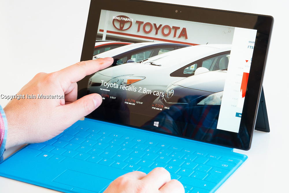Man reading Bing financial news about Toyota on a Microsoft Surface rt tablet computer