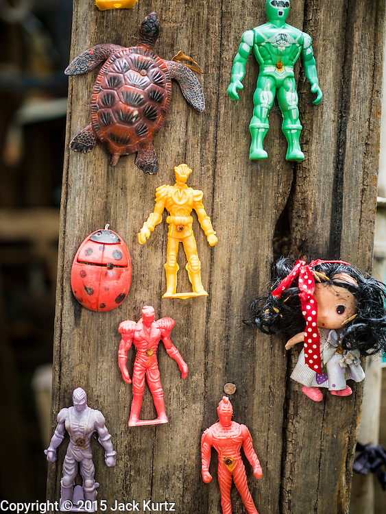 23 SEPTEMBER 2015 - BANGKOK, THAILAND: Old toys nailed to an exterior wall of a condemned home near Wat Kalayanamit. Fifty-four homes around Wat Kalayanamit, a historic Buddhist temple on the Chao Phraya River in the Thonburi section of Bangkok, are being razed and the residents evicted to make way for new development at the temple. The abbot of the temple said he was evicting the residents, who have lived on the temple grounds for generations, because their homes are unsafe and because he wants to improve the temple grounds. The evictions are a part of a Bangkok trend, especially along the Chao Phraya River and BTS light rail lines. Low income people are being evicted from their long time homes to make way for urban renewal.           PHOTO BY JACK KURTZ