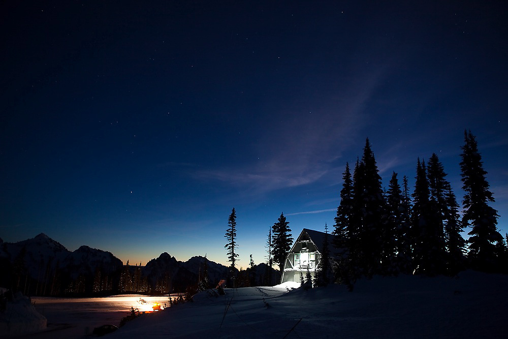 The cabin of the Rainier Mountaineering Inc. (RMI) guide service glows at night besides the parking lot at Paradise, Mount Rainier National Park, Washington.