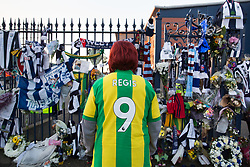 © Licensed to London News Pictures. 30/01/2018. The funeral of footballer Cyrille Regis took place in West Bromwich today. The hearse made it's way past the football ground where he played as family, friends and fans said their final farewell. Pictured, a fan bearing the Regis name and his number 9 outside the Hawthorns. Photo credit: Dave Warren/LNP