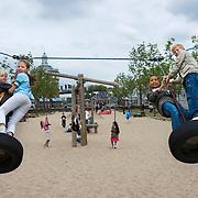 Nederland Rotterdam 25-09-2009 20090925 Foto: David Rozing  Kinderen hebben lol met het schommelen op grote rubberen banden in wijk Kralinger Esch, speeltuin zandbak. Children playing outside.                                              .Foto: David Rozing